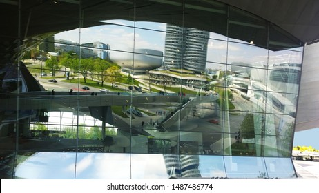 Munich, Bavaria / Germany - summer 2016: Modern futuristic architecture - BMW headquarters and museum reflected in glass facade of BMW World center