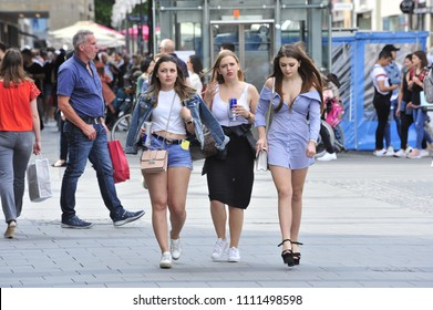 Munich, Bavaria/Germany- 05/21/2018: Three beautiful young girls walk through the Marienplatz holding energy drinks.