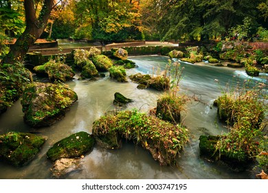 Munich English garden Englischer garten park and Eisbach river with artificial waterfall . Autumn colours on trees and leaves and flowing river. Munchen, Bavaria, Germany - Shutterstock ID 2003747195