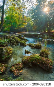 Munich English garden Englischer garten park and Eisbach river with artificial waterfall . Autumn colours on trees and leaves and flowing river. Munchen, Bavaria, Germany - Shutterstock ID 2004328118