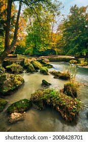 Munich English garden Englischer garten park and Eisbach river with artificial waterfall . Autumn colours on trees and leaves and flowing river. Munchen, Bavaria, Germany - Shutterstock ID 2008428701
