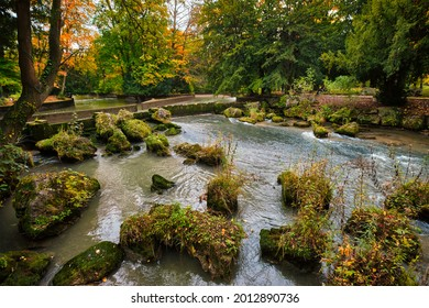 Munich English garden Englischer garten park and Eisbach river with artificial waterfall . Autumn colours on trees and leaves and flowing river. Munchen, Bavaria, Germany - Shutterstock ID 2012890736