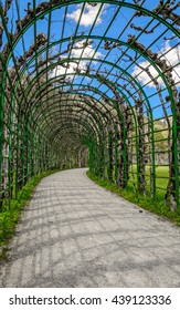 MUNICH (ETTAL, FUSSEN) GERMANY - 06 MAY 2016: Magic view with blue sky and clouds outside the green archway (tunnel) in a gardens surrounding of the Linderhof Palace