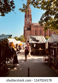 MUNICH, GER - AUGUST 1, 2018: Auer Dult, a funfair with market stalls. People standing, watching and buying jumble or some eats . Church Mariahilf with clear blue sky and leaves in the foreground.