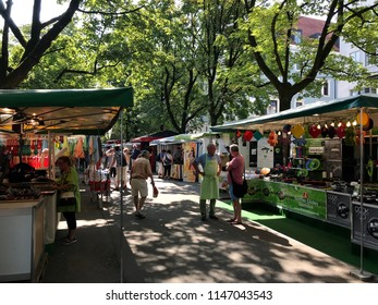 MUNICH, GER - AUGUST 1, 2018: Auer Dult, a funfair with market stalls, green roofs, colorful jumble. People standing and talking or walking. Sunny day with trees, providing shade. Houses  background.