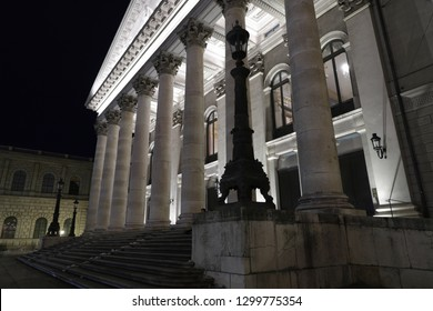 MUNICH, GER - JANUARY 16, 2019: Night view of the illuminated opera house -Nationaltheater. Famous classicist building in the city. Low angle view with colums, windows, ornaments, lantern. No persons.