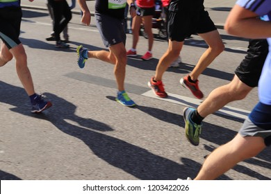 MUNICH, GER - OCTOBER 14, 2018: Running feet with sports shoes at the GENERALI MÜNCHEN MARATHON. Legs with short trousers, calves and colorful shoes in motion. Selective focus, intentional blurry.