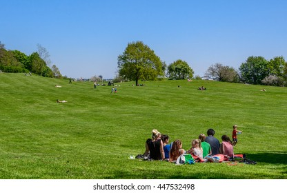 MUNICH, GERMANY - 08 MAY 2016: Back view to the family relaxes (picnicking) on the lawn in the park - little boy running to his family, which are sitting on the perfectly manicured green grass