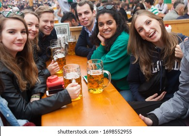 MUNICH, GERMANY- 10 October 2018: Young students are drinking alcohol and enjoying their time at the Oktoberfest beer cultural festival in Munich, Germany