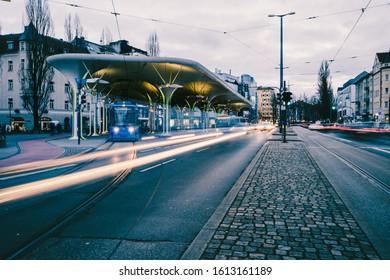 """Munich, Germany - 12.01.2020: Night time lapse of famous public transport station """"Münchner Freiheit"""" in munich. Evening rush hour with busy street life. Traffic light trails."""