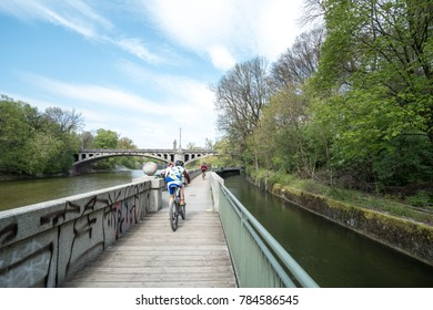 Munich, Germany - 21 April 2017 : View of people cycling along the path with building at the river bank of Isar river in Munich.
