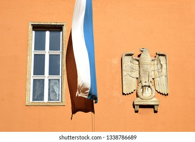 MUNICH, GERMANY - 25 FEBRUARY 2019: Bavarian flag and eagle of the Third Reich still displayed together on the front wall of the Bavarian State Tax Office which the NSDAP built between 1938 and 1941