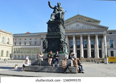 MUNICH, GERMANY - 25 FEBRUARY 2019:  People enjoy winter sunshine on Maximilian Joseph's statue in Max-Joseph-Platz in front of the Nationall Theatre, home of the state opera and ballet companies.