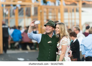 MUNICH, GERMANY - 25 SEPTEMBER 2016: A couple dressed in traditional bavarian clothes take a selfie in the Oktoberfest grounds.