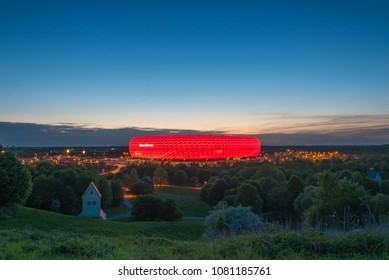 MUNICH, GERMANY - 29 April 2018: Aerial view of Allianz Arena, the football stadium of FC Bayern, illuminated in red at the dusk from Fröttmanninger Berg