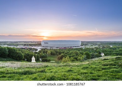 MUNICH, GERMANY - 29 April 2018: Aerial view of Allianz Arena, the football stadium of FC Bayern, illuminated in red during sunset from Fröttmanninger Berg