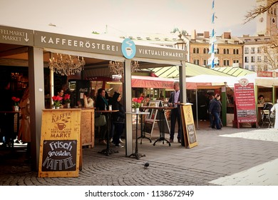 MUNICH, GERMANY - APRIL 5, 2018 - Coffee bar at Viktualienmarkt in Munich center, it is early spring but visitors enjoy a warm espresso outside