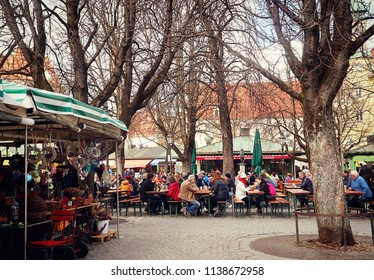 MUNICH, GERMANY - APRIL 5, 2018 - Beer garten at Viktualienmarkt in Munich center, it is early spring but habitués and tourists drink and eat outside, enjoying the warm weather