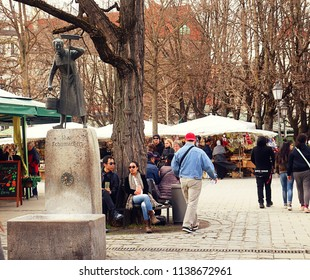 MUNICH, GERMANY - APRIL 5, 2018 - view of Viktualienmarkt gourmet market with cozy atmosphere in Munich center with the memorial fountains of the folk singers and comedians Ida Schumacher