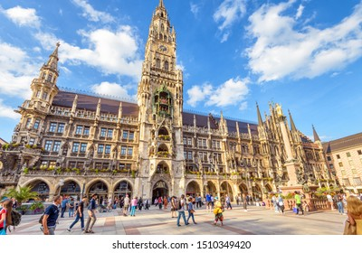 Munich, Germany – Aug 1, 2019: People visit nice Marienplatz square in Munich. Panorama of Town Hall or Rathaus in summer. It is a famous Gothic landmark of Munich. Concept of travel in Munich city.