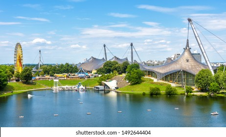 Munich, Germany - Aug 2, 2019: Olympiapark in summer. It is Olympic Park, landmark of Munich. Scenic view of former sport area. Panorama of the green Munich district with lake. Skyline of Munich city.
