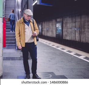 Munich, Germany - Aug. 23, 2019: Old man standing in munich subway checking phone for train time escalator in background