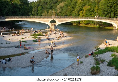 Munich Germany - Aug 28, 2019: Sunset at munich Isar river with people walking sitting bathing happy fun summer evening. People can swim in munich Isar river