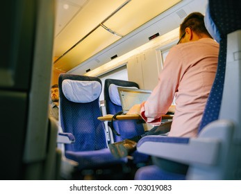 MUNICH, GERMANY - AUG 8, 2017: German worker inside fast ICE train commuting worker on laptop for the next important project - commuting home or going to work