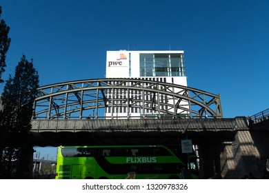 Munich, Germany - August 15, 2018: MeinFernbus FlixBus green bus passing near a building with the PwC signage. PricewaterhouseCoopers is a multinational professional services network