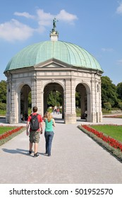 MUNICH, GERMANY - AUGUST 17, 2011: Couple of tourists, walk to the temple of Diana, strolling through the gardens of Hofgarten