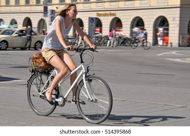 MUNICH, GERMANY - AUGUST 17, 2011: Young woman riding a bicycle through the city center