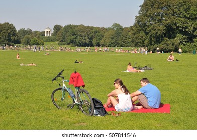 MUNICH, GERMANY - AUGUST 18, 2012: Couple sitting on the grass next to his bike, basks in the English garden