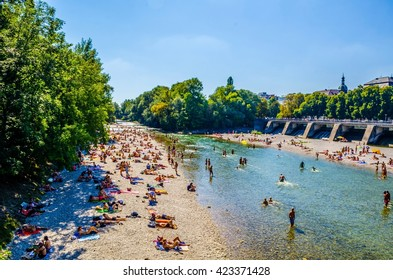 MUNICH, GERMANY, AUGUST 20, 2015: People enjoy sunny hot weather on the river banks of Isar river in bavarian city Munich. The river becomes a giant beach during hot days.