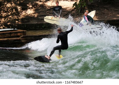 MUNICH, GERMANY, August 26, 2018: Surfer on the stream (German Eisbach) in the English Garden