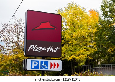 Munich, Germany, Bavaria - October 30 2018. Pizza Hut Sign in fall with yellow trees in front of a Pizza Hut Restaurant