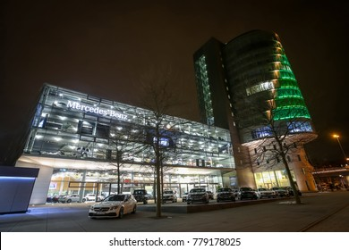 MUNICH, GERMANY - DECEMBER 11, 2017 : Exhibited cars parked in front of the Mercedes Benz dealership building at night in Munich, Germany.