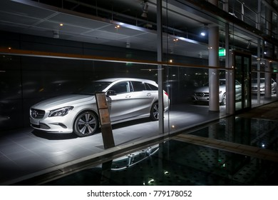 MUNICH, GERMANY - DECEMBER 11, 2017 : A view of the Mercedes Benz dealership building exterior with cars exhibited in the shop window at night in Munich, Germany.