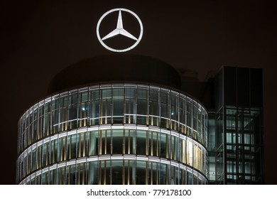 MUNICH, GERMANY - DECEMBER 11, 2017 : A view of the Mercedes Benz dealership office building exterior with the company logo on the top at night in Munich, Germany.