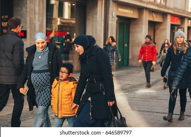 Munich, Germany, December 29, 2016: A friendly family of migrants walks down the street in Munich.