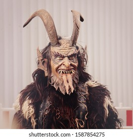 MUNICH, GERMANY - DECEMBER 8, 2019 Performer with wooden chiseled mask and horns at theTraditional Krampus run  in Munich center, demonic and evil masked figure  of pre-Christian times
