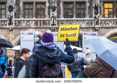 MUNICH / GERMANY - FEBRUARY 15 2018: Lady is raising a sign against the PEGIDA demonstration, Translation: Munich is colourful