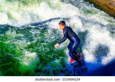 MUNICH, GERMANY, February 18 2019: Surfer at cold water of river Eisbach in Munich, Germany.