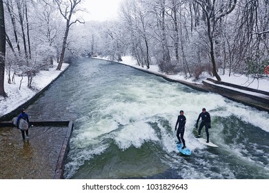 MUNICH, GERMANY - FEBRUARY 20, 2018  Munich, surfers riding the artificial wave on the Eisbach, small river across the Englischer Garten, in a freezing February morning