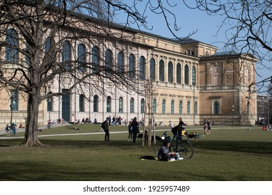 Munich, Germany - February 24, 2021: People enjoying spring weather on the lawn outside the Alte Pinakothek museum.