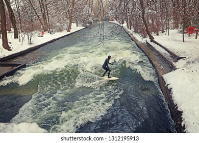 MUNICH, GERMANY - FEBRUARY 5, 2019 - Munich, surfer rides the artificial wave on the Eisbach, small river across the Englischer Garten, in a freezing February morning