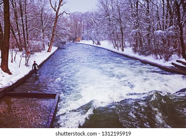 MUNICH, GERMANY - FEBRUARY 5, 2019 - Munich, surfer ready to ride the artificial wave on the Eisbach, small river across the Englischer Garten, in a freezing February morning