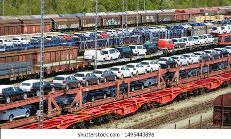 Munich, Germany - July 10, 2019: lots of new cars loaded on railway autorack wagons and ready for shipment from factories to automotive distributors