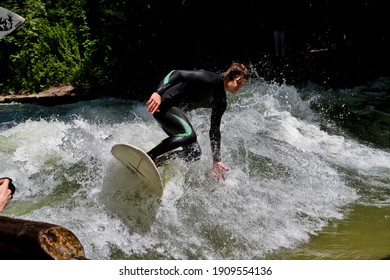 Munich, Germany - July 13, 2019: Surfer in the city river, Munich is famous for people surfing in urban enviroment called Eisbach