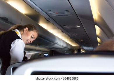 Munich, Germany - July 16, 2017:  A female flight attendant  is speaking with a passenger sitting in the economy class of the route Munich - Vancouver of Lufthansa Airlines.