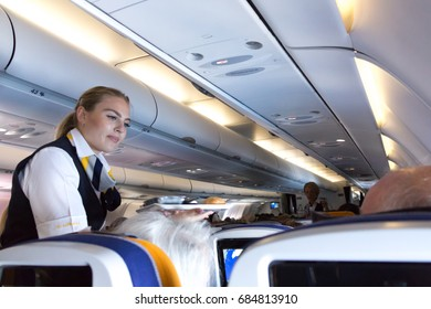 Munich, Germany - July 16, 2017:  A female flight attendant is serving the lunch to a passenger sitting in the economy class of the route Munich - Vancouver of Lufthansa Airlines.
